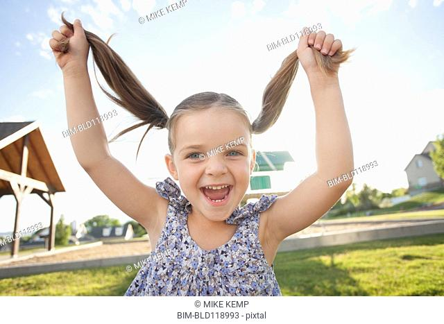 Caucasian girl playing with pigtails outdoors