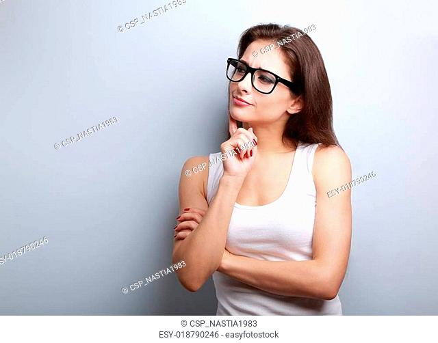 Thinking serious young woman in glasses looking on empty copy space