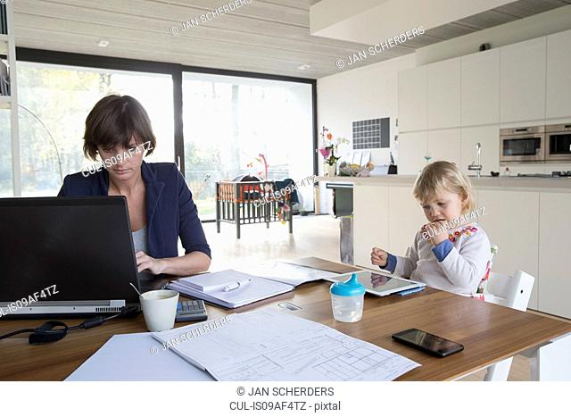 Mother with female toddler working on computer at kitchen table