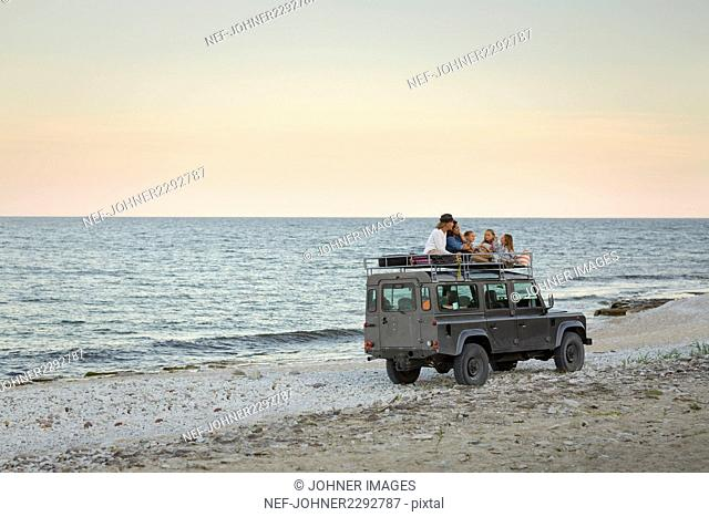 Tourists traveling on roof of jeep