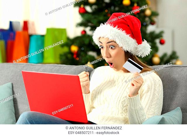 Amazed woman buying gifts on line in christmas