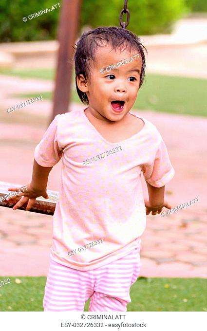Asian baby girl playing in playground alone
