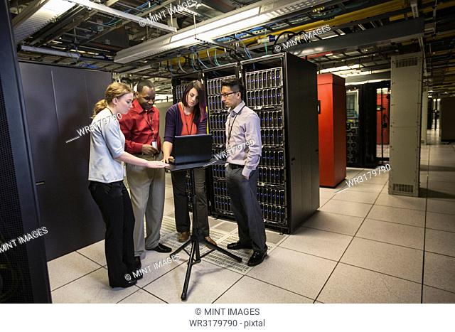 Mixed race group of technicians doing diagnostic tests on servers in a large server farm