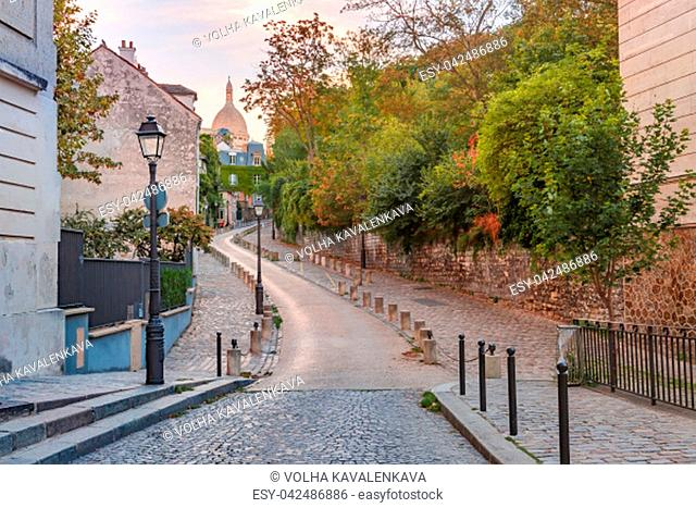 Empty cosy street and dome of Sacre-Coeur in the morning, quarter Montmartre in Paris, France