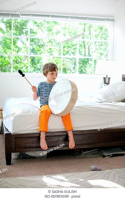 Boy drumming on bed