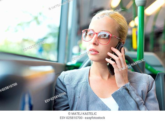 Blonde caucasian business woman talking on cell phone, traveling by bus. Public transport and commuting to work