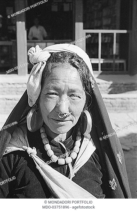 Nepalese woman with typical earrings on her ears and nose. Nepal, 1965