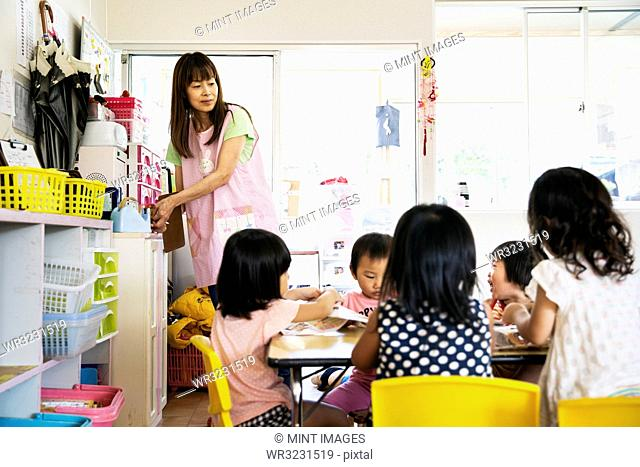 A young woman teacher and group of children in a Japanese preschool seated at a table