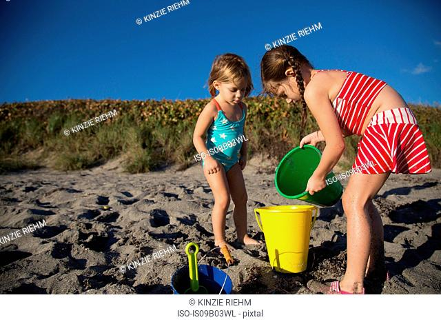 Girl and sister playing with toy buckets on beach, Blowing Rocks Preserve, Jupiter Island, Florida, USA