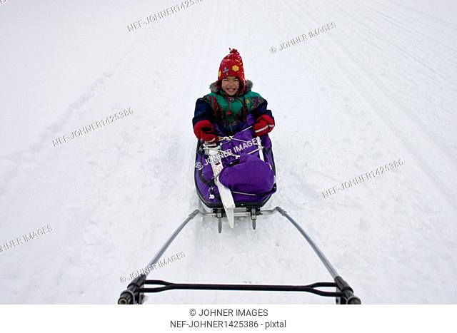 Girl on sled pulled by vehicle
