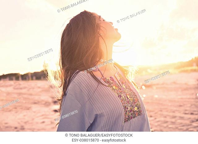 Latin beautiful girl happy in Caribbean beach sunset with embroidery dress portrait