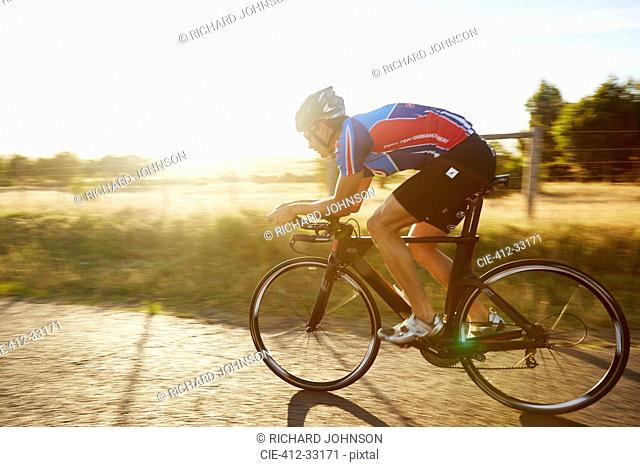 Male cyclist cycling on sunny sunrise rural road