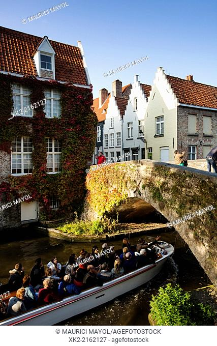 Group of tourists in a boat tour under the bridge in Bruges, Flanders, Belgium