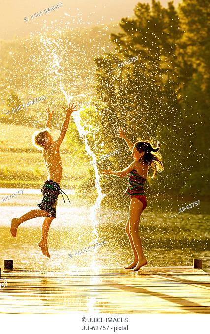 Young boy and girl jumping in air on jetty through splash of water