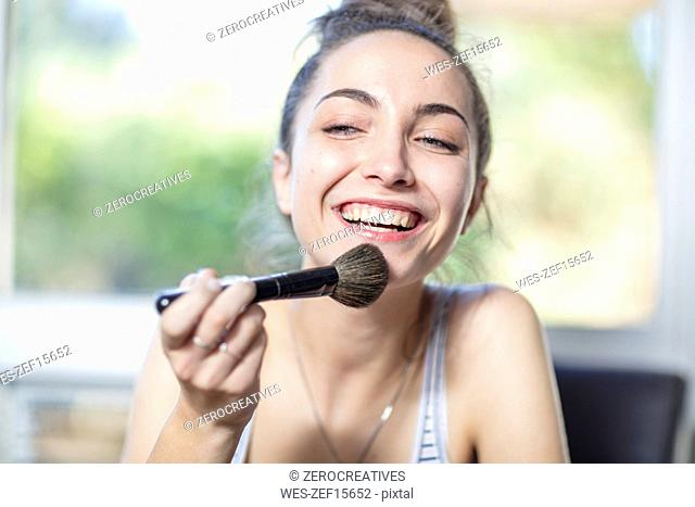 Happy teenage girl applying makeup