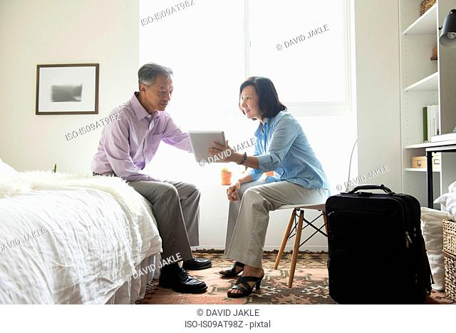 Mature couple sitting in hotel room with suitcase using digital tablet