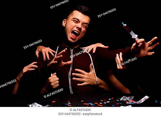 A handsome young student screaming, suffering from deadly drug cravings on the black background. A hallucinating addict sitting next to a table with various...