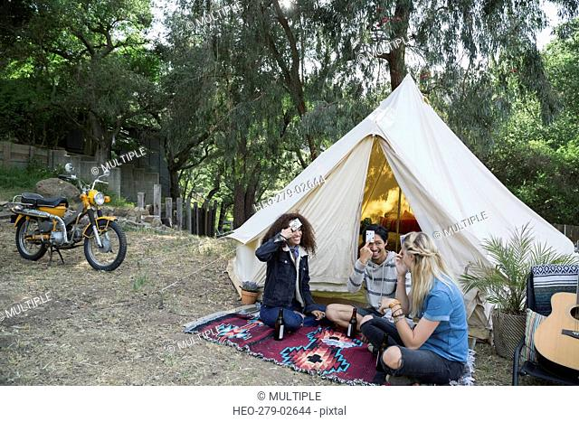 Young friends playing card game outside camping yurt