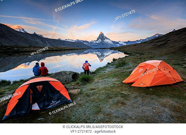 Photographer in action with Matterhorn reflected in Lake Stellisee at dawn Zermatt Canton of Valais Switzerland Europe