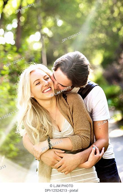 A young couple shares a romantic moment together in an embrace on a pathway on the university campus; Edmonton, Alberta, Canada
