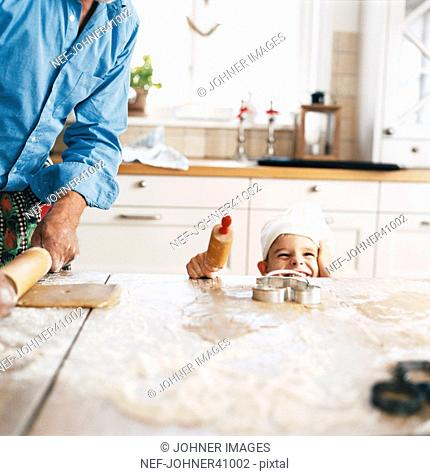 Smiling boy baking with his father