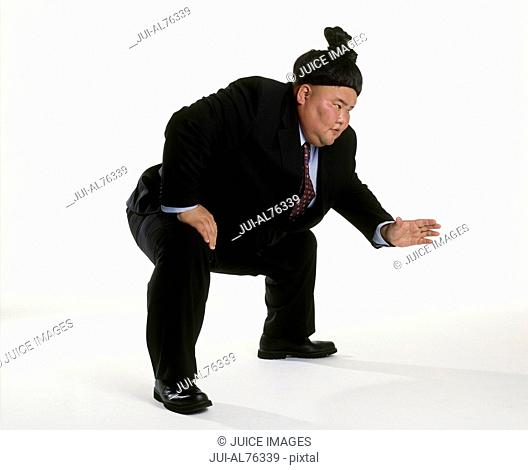 View of a sumo wrestler in a business suit squatting