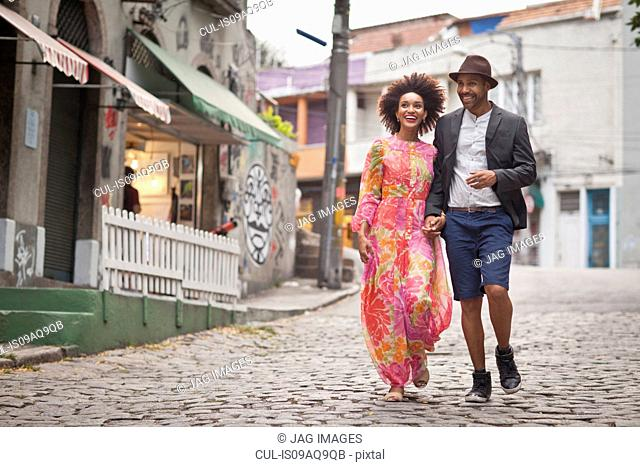 Couple walking along cobbled street, hand in hand
