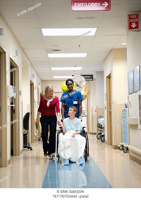 Nurse and mother walking behind boy's 10-11 wheelchair