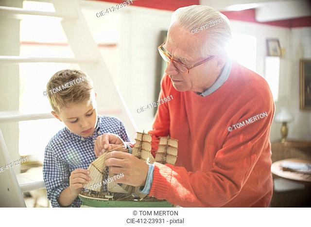Grandfather and grandson building model sailboat