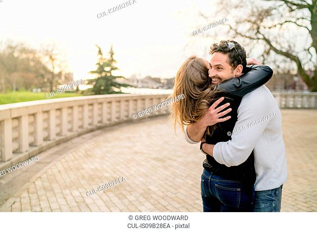 Young happy couple hugging in Battersea Park, London, UK