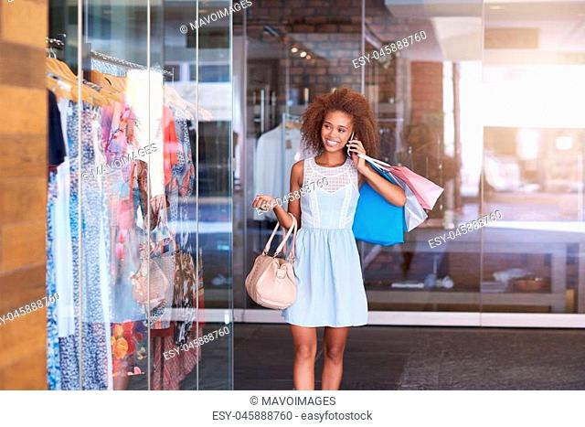 Attractive young woman with curly hair talking on her cellphone and carrying shopping bags while walking through a shopping mall