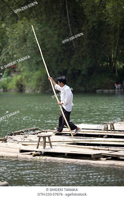 Raft on a bamboo raft at the Big banyan tree park Darongshu park, Yangshuo, Guilin, China