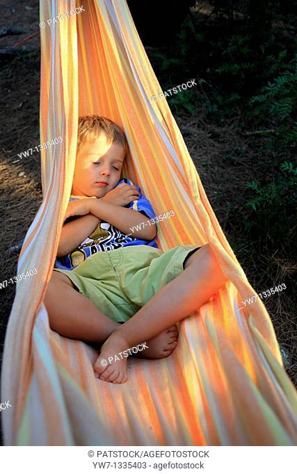 Boy aged 4 resting in a hammock