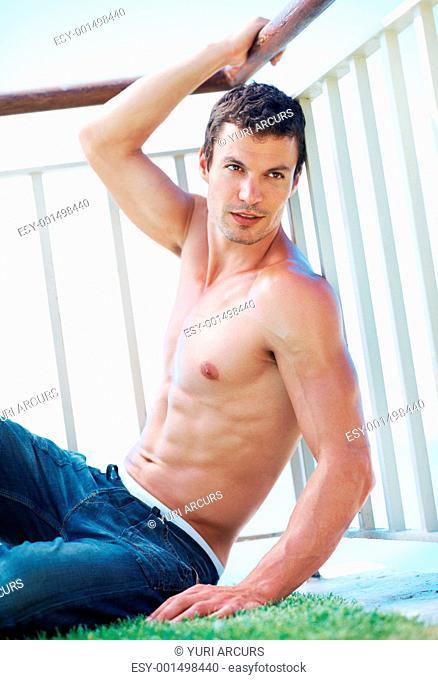 Handsome shirtless muscular man posing next to railings