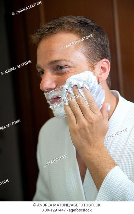Man putting shaving cream on face