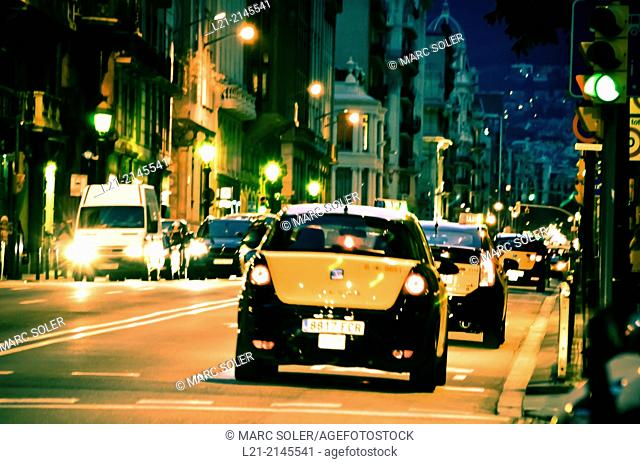 Traffic at street, taxis, night. Barcelona, Catalonia, Spain