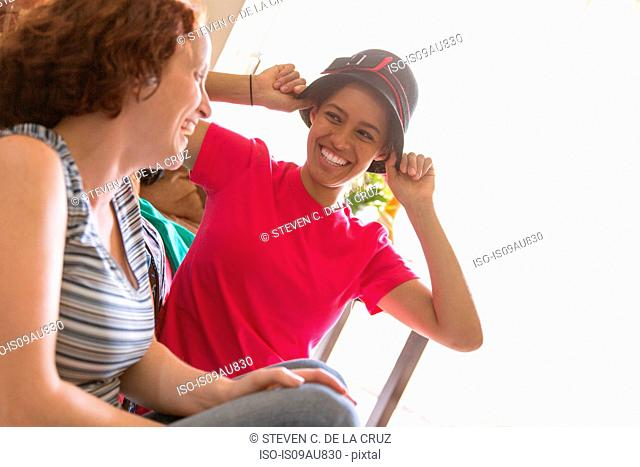 Young women trying on hat face to face smiling