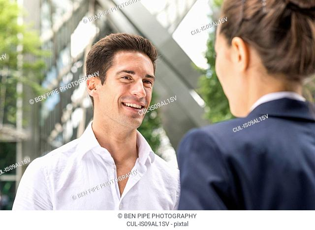 Young businessman and woman chatting at Broadgate Tower, London, UK