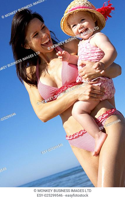 Mother With Young Daughter Running Along Beach Together