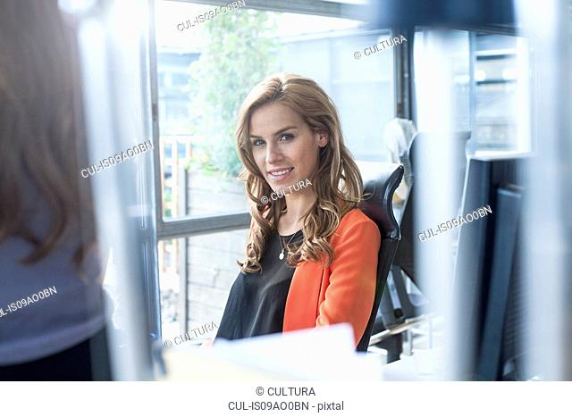Portrait of young businesswoman at office desk