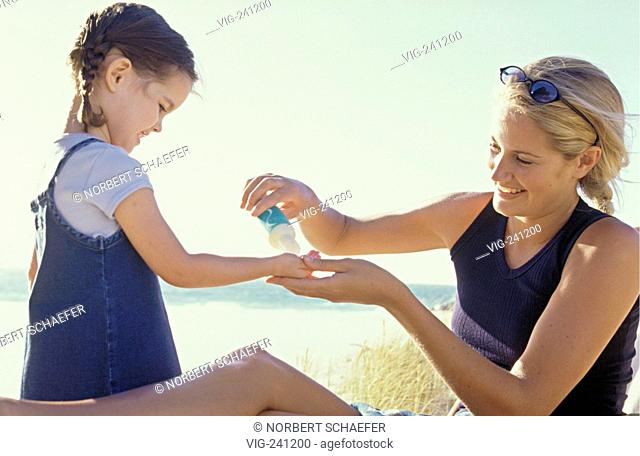 portrait, beach scene, mother applies cream on the arms of her 4 years old daughter to protect her against the sun at the coast  - GERMANY, 27/01/2004