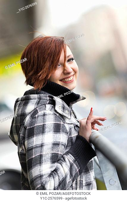 Teenager girl laughing looking at camera with small finger raised