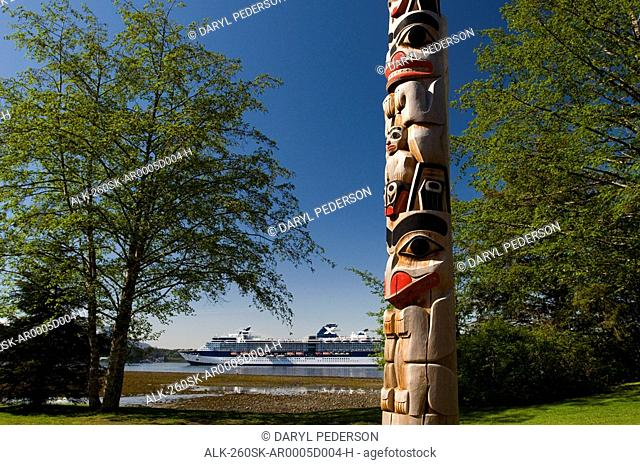 Totem pole with the coastline and a cruiseship in the background, Sitka National Historic Park, Alaska