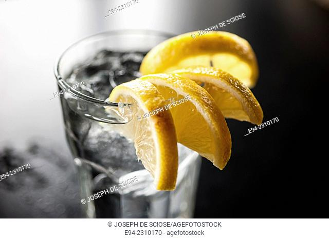 A glass of water with lemon wedges on the edge of a glass on a table in a restaurant, Alabama