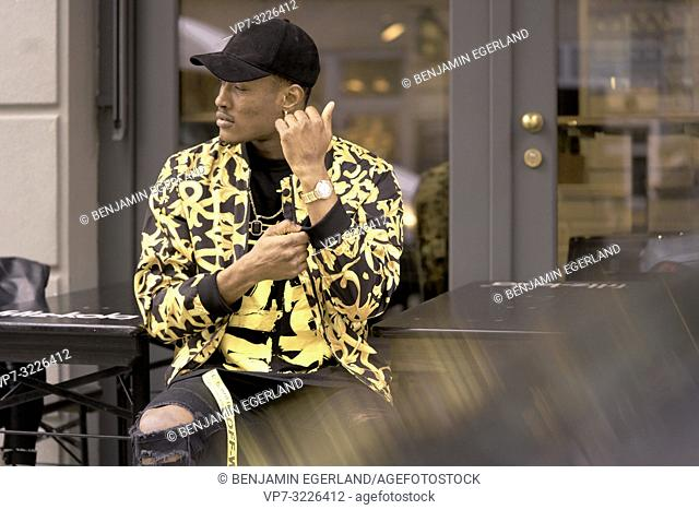 stylish man wearing wristwatch and individual fashion, adjusting clothes, sitting outdoors in city, in Munich, Germany