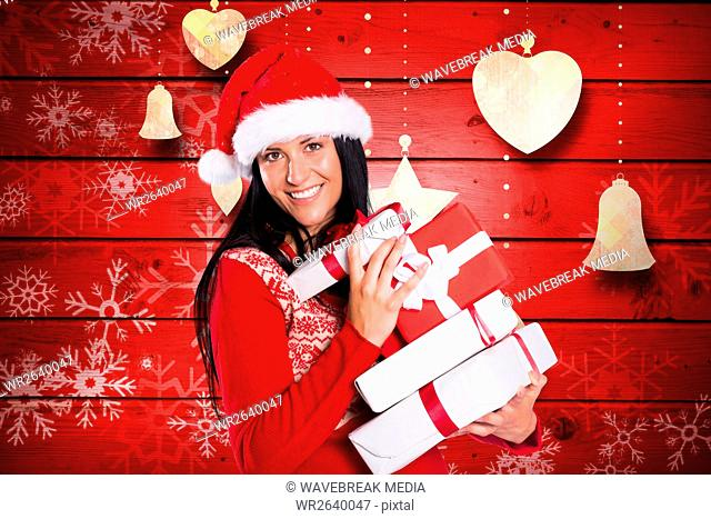 Happy woman in santa hat holding stack of christmas gifts