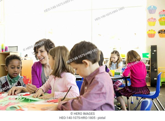 Smiling teacher with students in elementary class