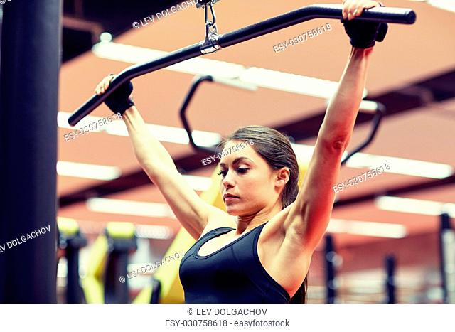 sport, fitness, bodybuilding, lifestyle and people concept - woman flexing arm muscles on cable machine in gym