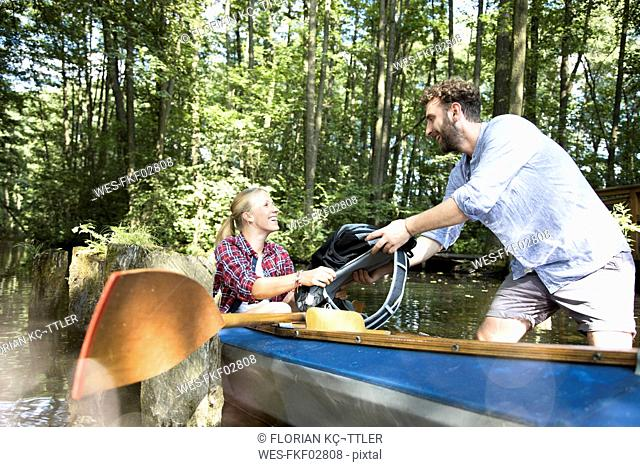 Happy young couple entering canoe in a forest brook