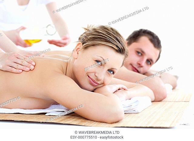 Positive young couple receiving a back massage with oil in a health spa